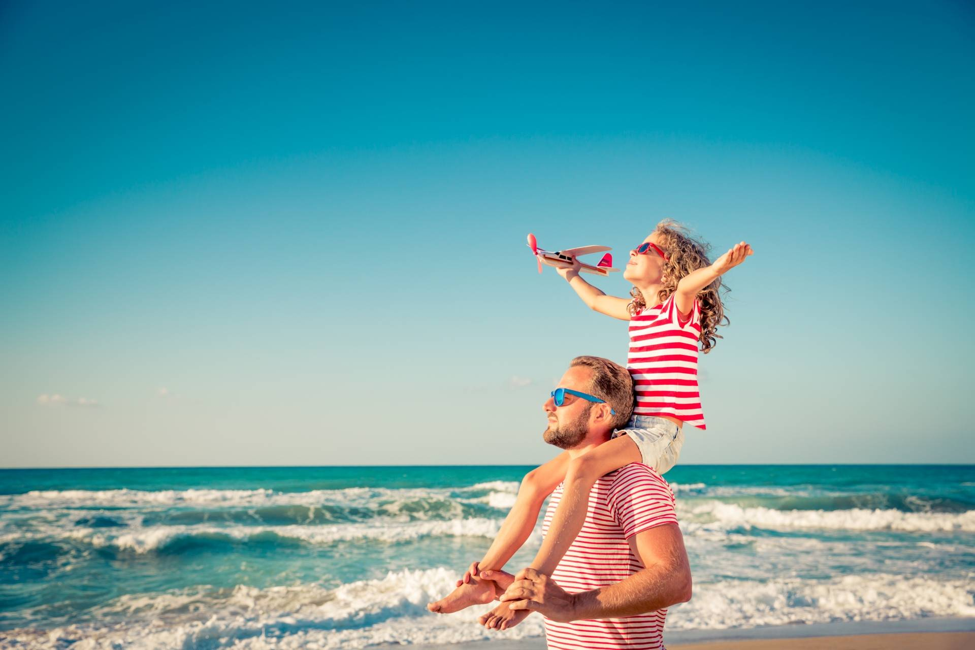 Dziewczynka siedzi u taty na barana i bawi się małym samolotem na plaży. Jak chronić dziecko przed udarem słonecznym?