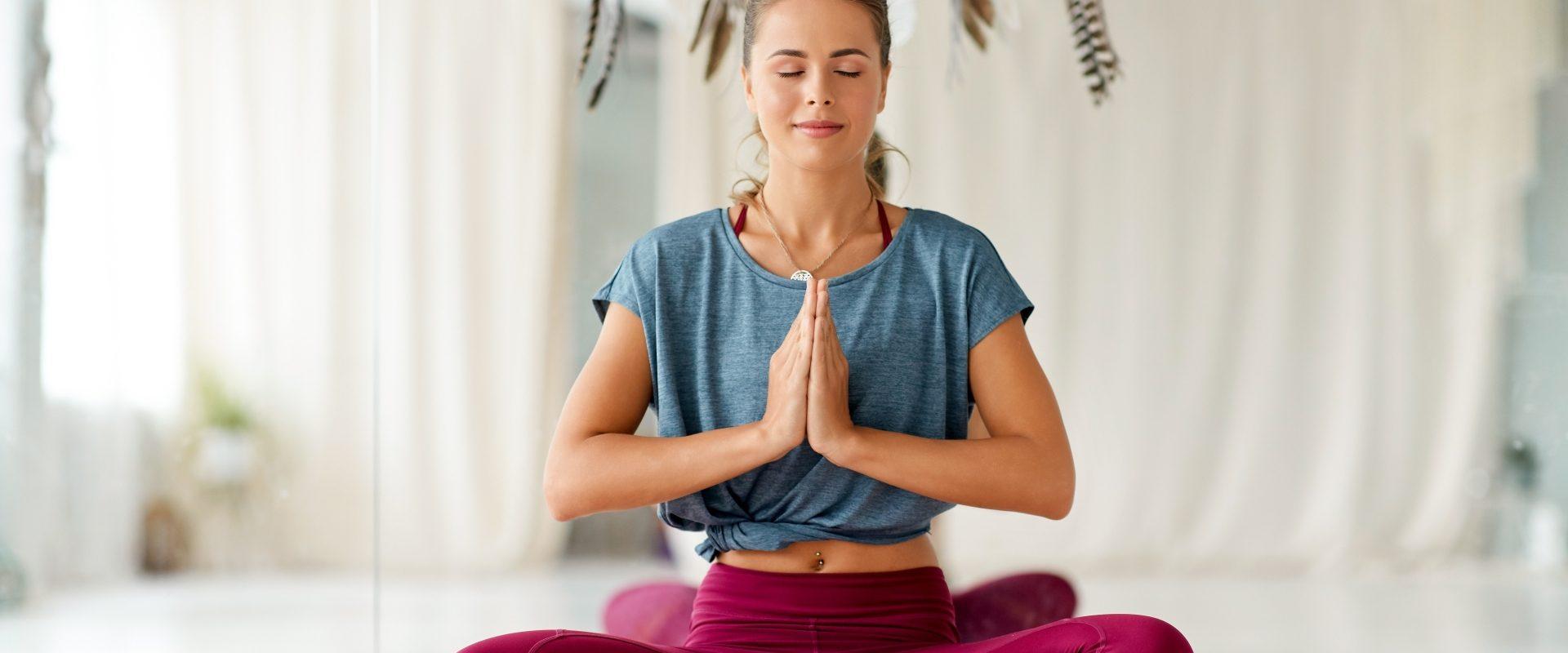 Techniki relaksacyjne - jakie warto znać? Kobieta w trakcje medytacji siedzi w pozycji kwiatu lotosu.