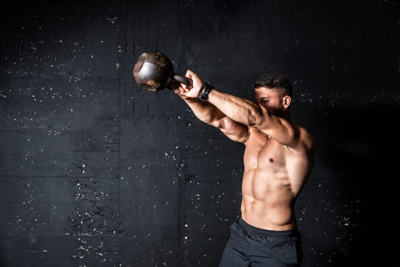 Jak podnieść testosteron? O niedoborze testosteronu u mężczyzn opowiada dr n. med. Ewa Kempisty-Jeznach. Umięśniony mężczyzna bez koszulki ćwiczy na siłowni z kettle ballem na tle czarnej ściany.