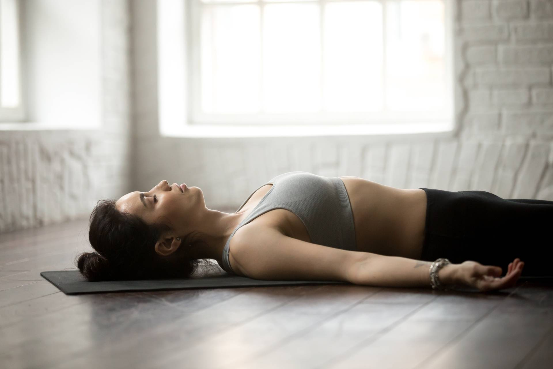 Trening autogenny - na czym polega? Kobieta relaksuje się leżąc na macie.