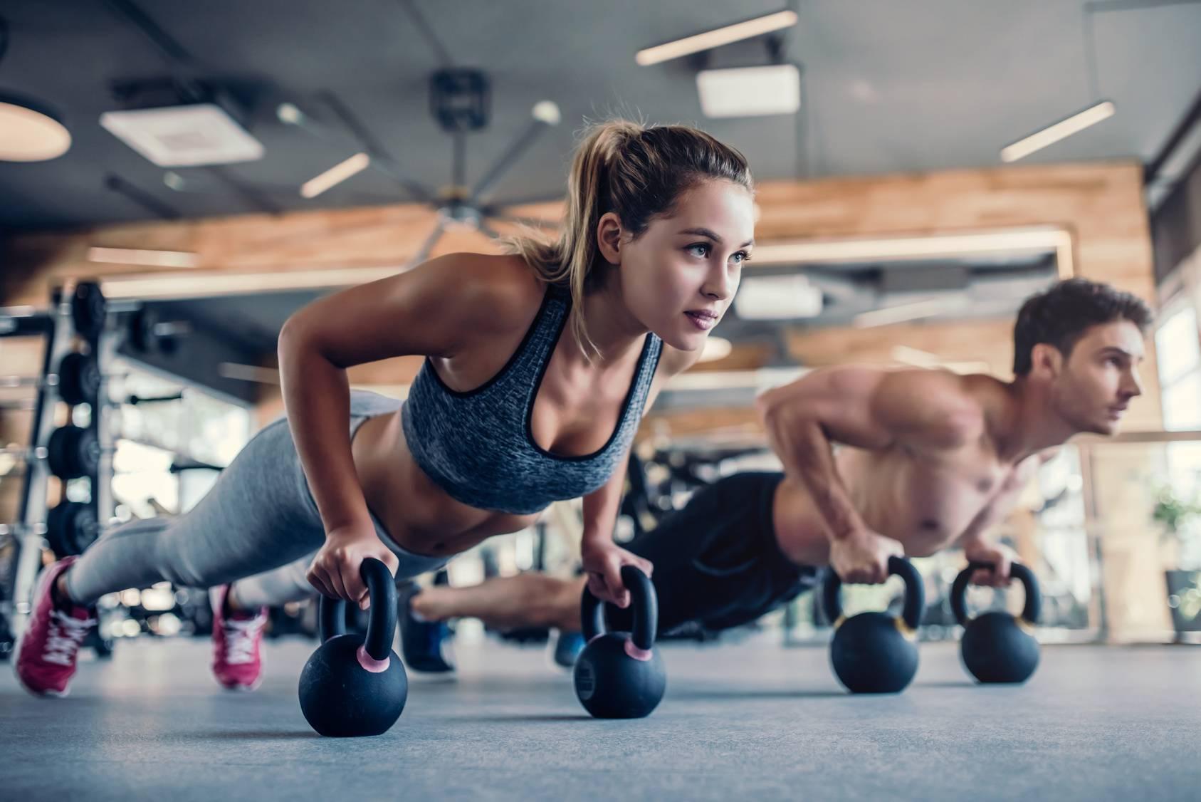 Sprawdź ćwiczenia płaski na brzuch. Kobieta i mężczyzna wykonują trening siłowy na siłowni.