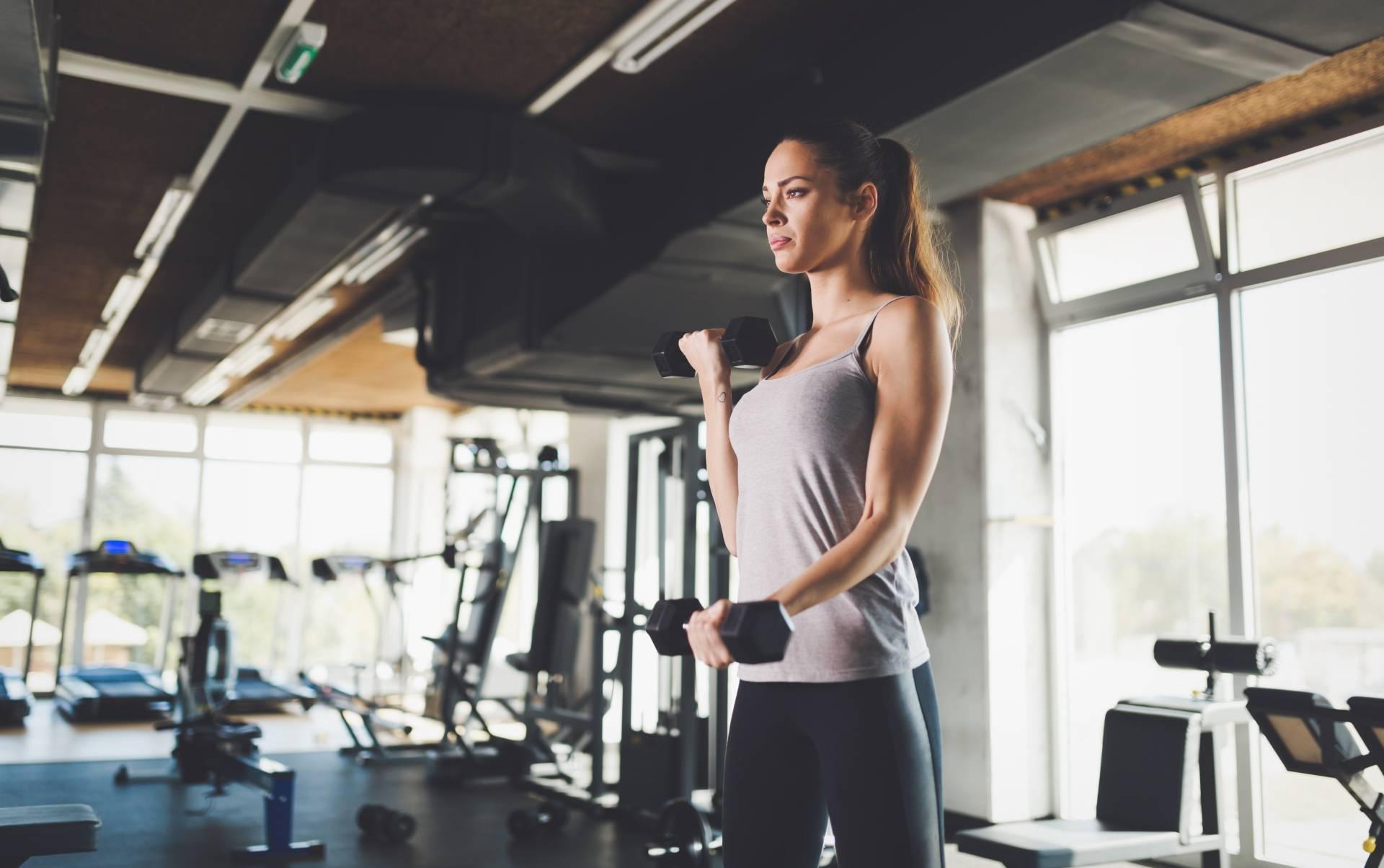Ćwiczenia na proste plecy - jak wygląda prawidłowa postawa? Kobieta ćwiczy na siłowni z hantlami.