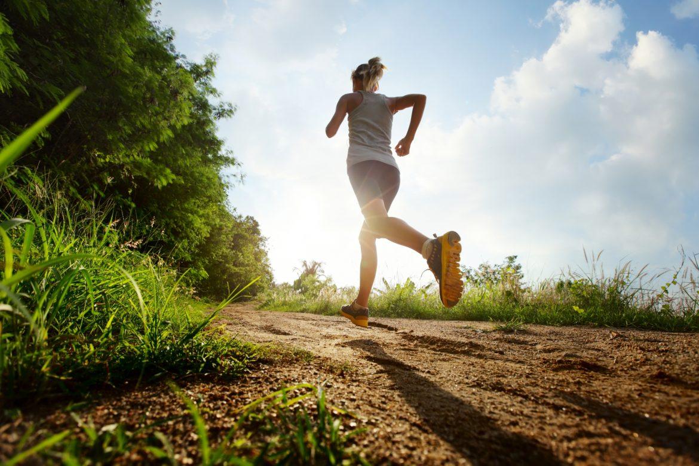 Trening na świeżym powietrzu - jak go wykonać? Fartlek i trening siłowy. Młoda wysportowana kobieta uprawia jogging na łonie natury.