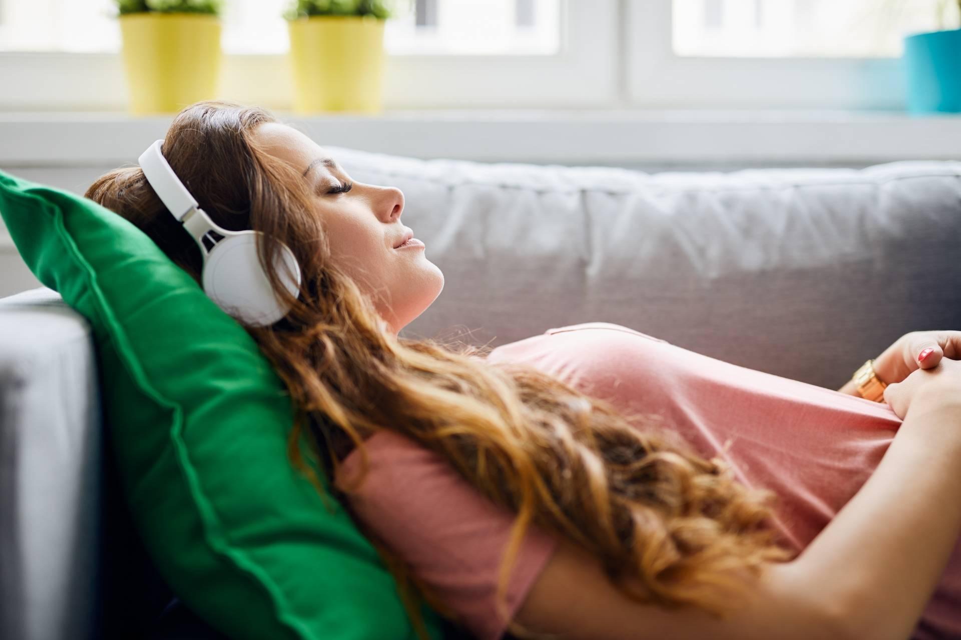 Trening autogenny Schultza - na czym polega relaksacja? Kobieta relaksuje się na kanapie słuchając muzyki.