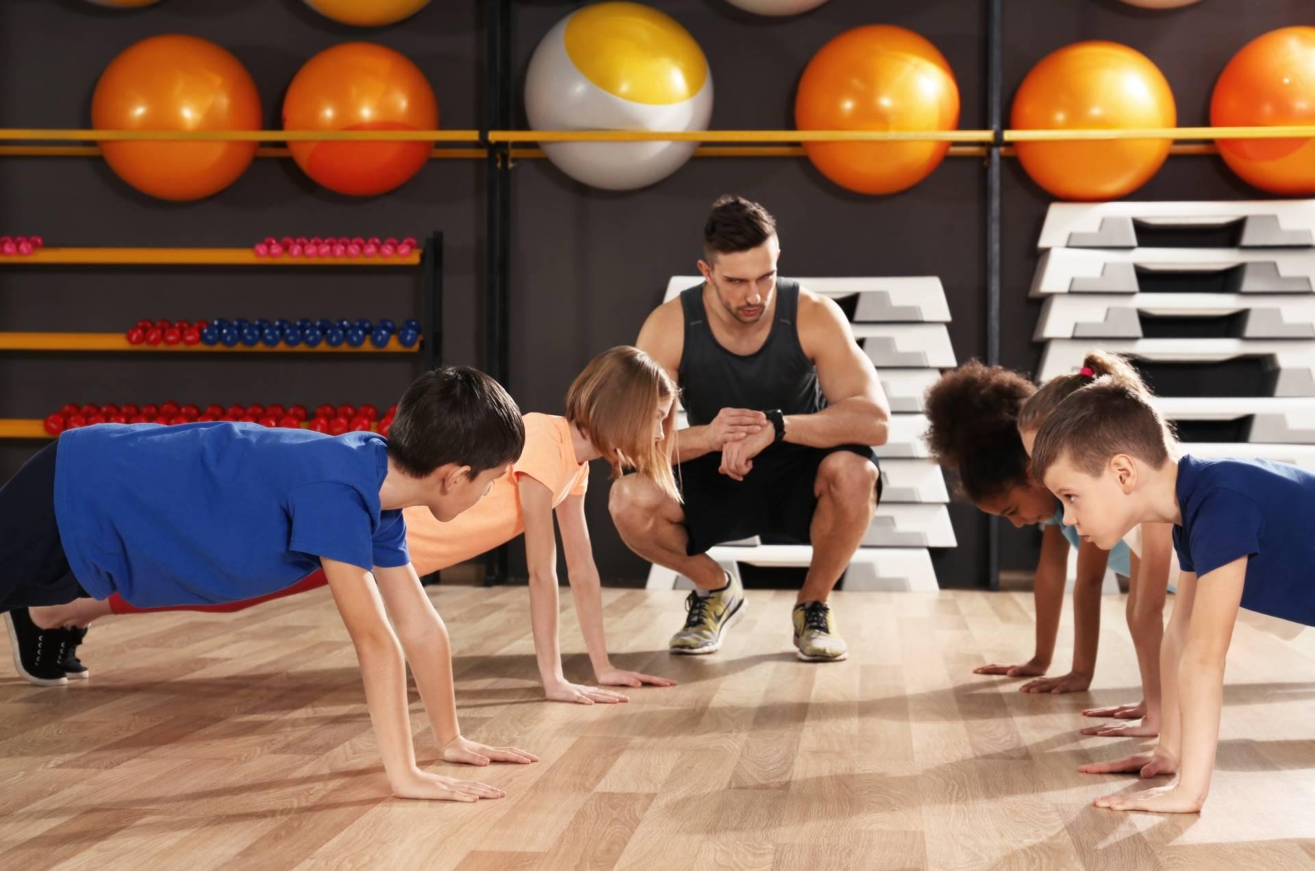 Trening siłowy dla dzieci z trenerem na zajęciach.