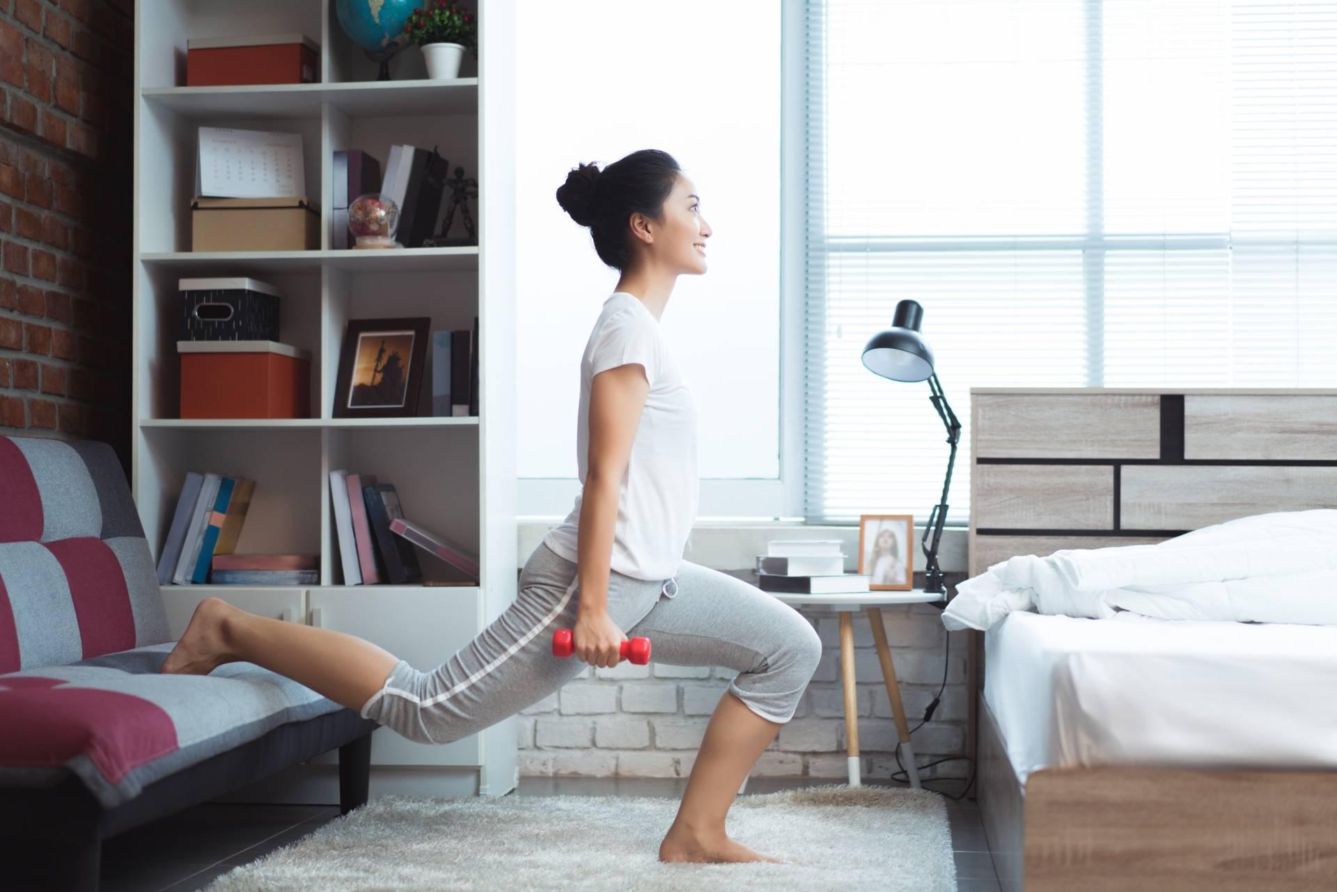 Zaparcia - jakie mogą być przyczyny? Młoda Azjatka ćwiczy w domu z ciężarkami.