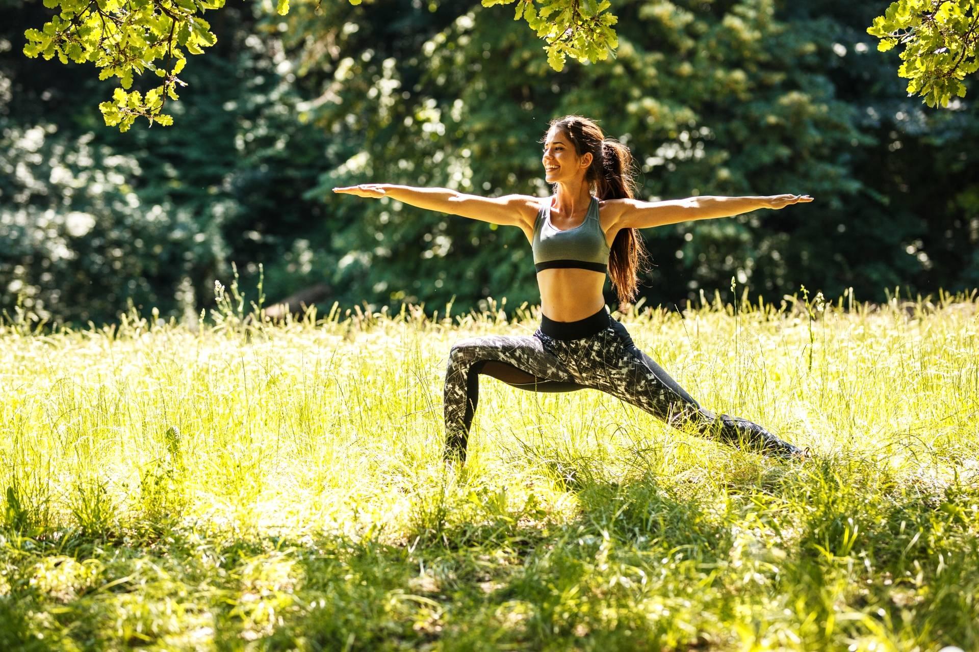 Trening w parku. Młoda wysportowana kobieta ćwiczy w parku.