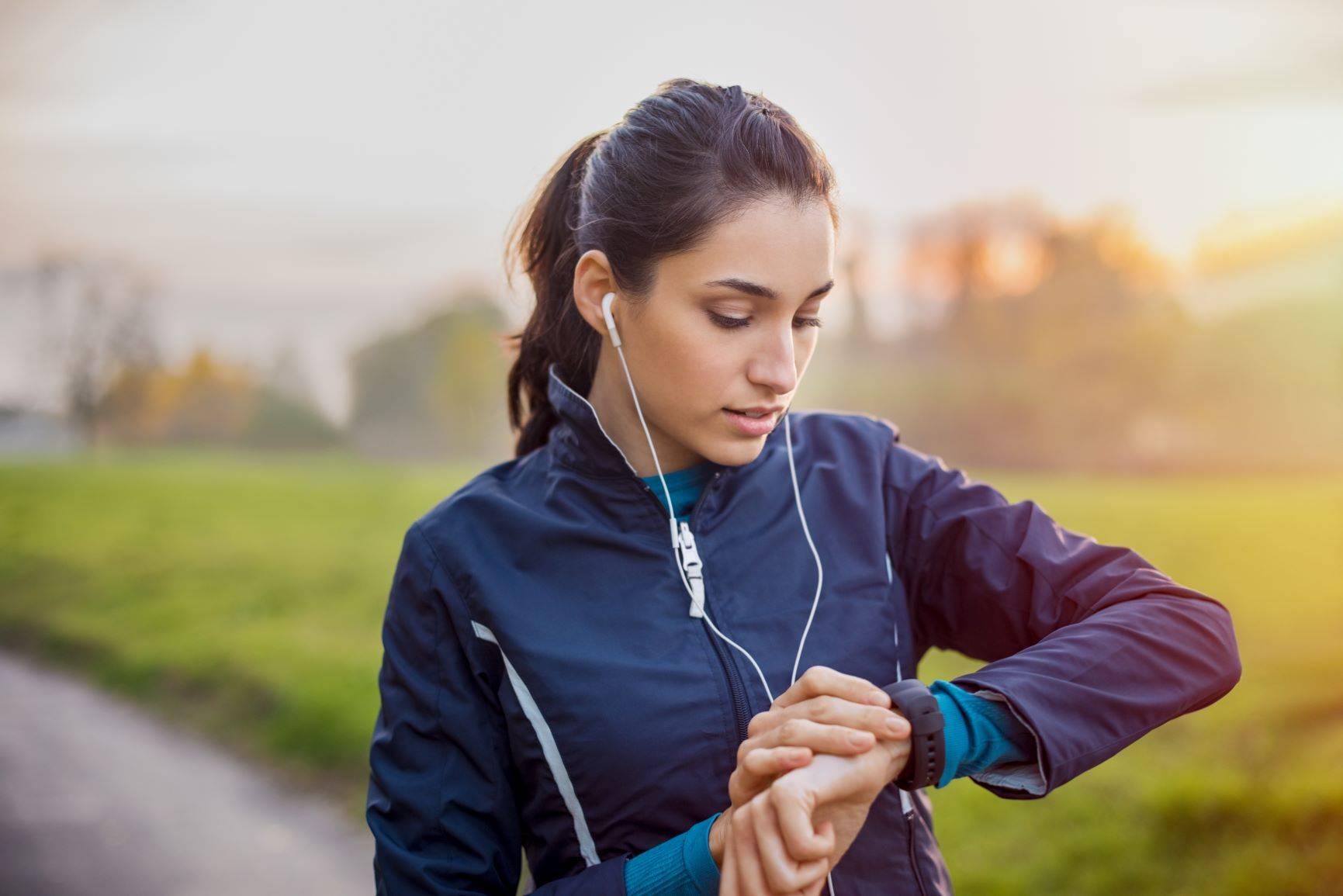 Trening z pulsometrem - czy warto? Młoda wysportowana kobieta uprawia jogging i sprawdza puls.