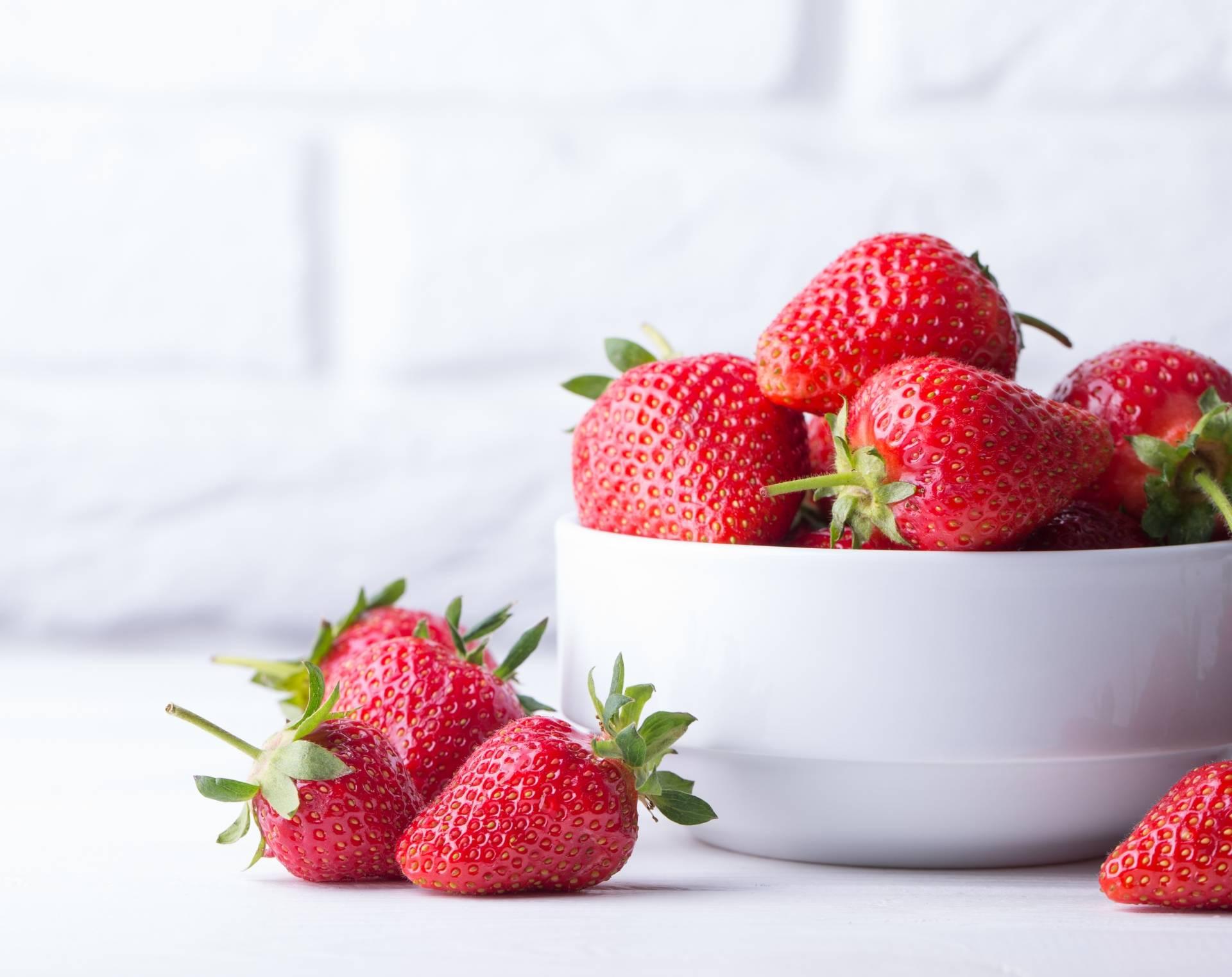 Truskawki - przepisy na letnie dania. Truskawki w białej misce na białym tle.