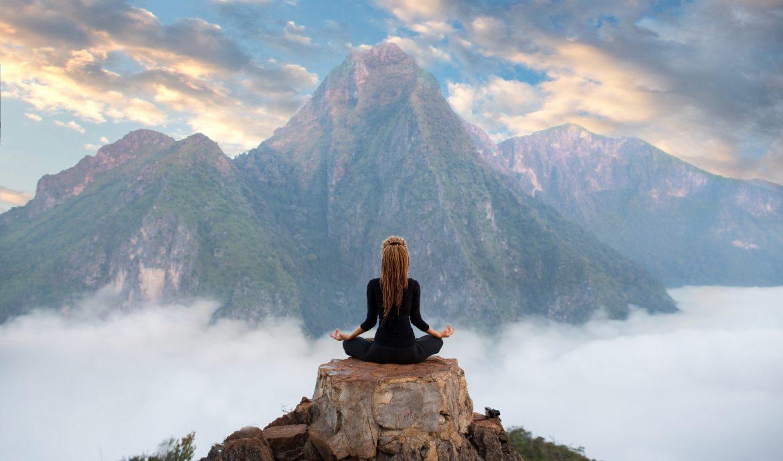 Rytuały tybetańskie, które warto wcielić w życie. Kobieta medytuje siedząc na skale ponad chmurami w Tybecie.