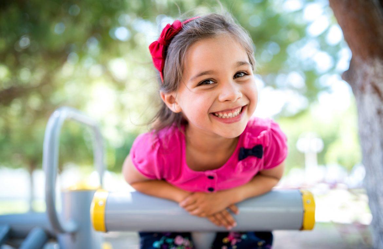 Dr Katarzyna Simonienko o swobodnej zabawie dzieci na świeżym powietrzu. Mała dziewczynka w różowej bluzce bawi się na placu zabaw na dworze latem.
