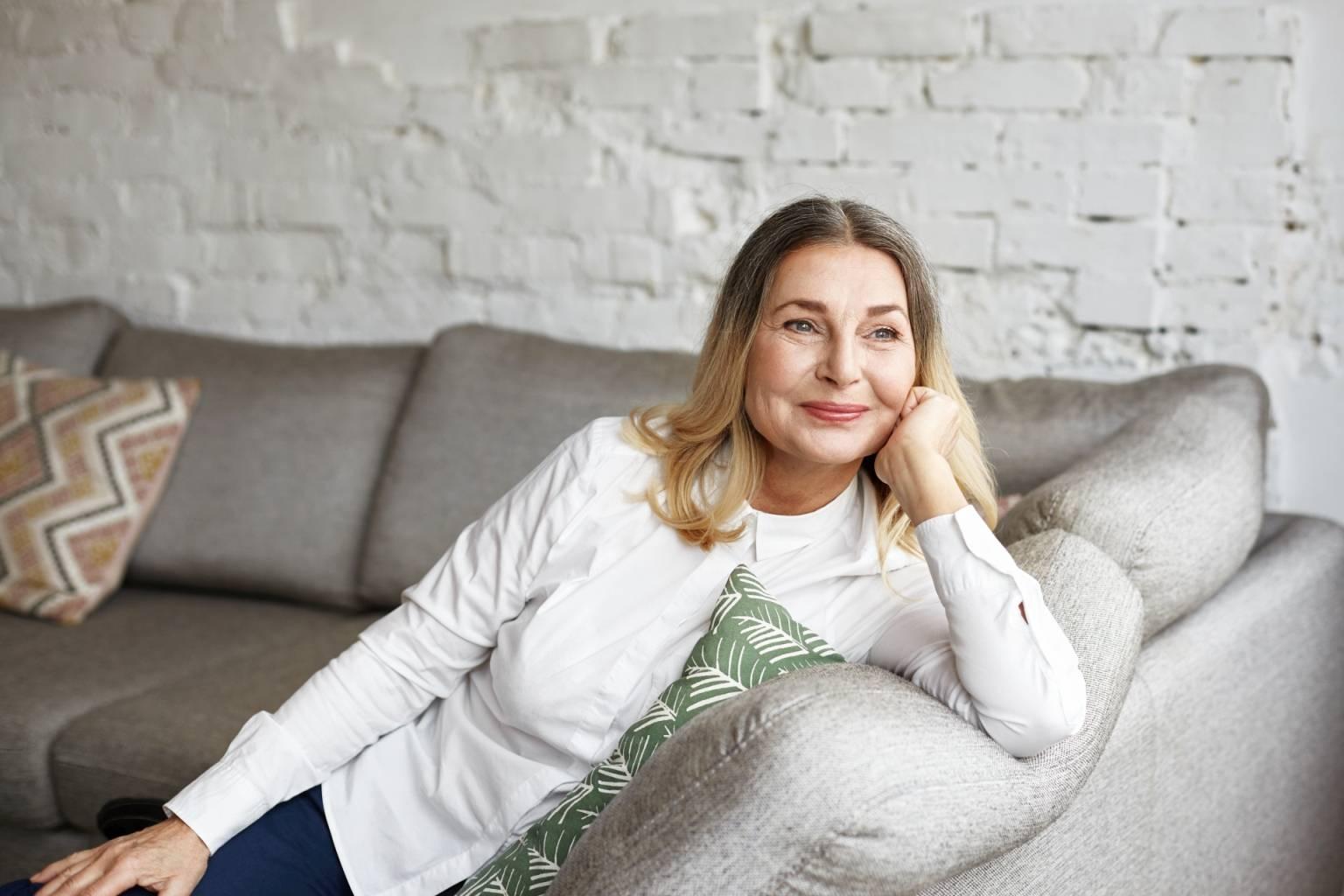 Leki homeopatyczne na menopauzę. Uśmiechnięta seniorka siedzi na kanapie w domu i wygląda przez okno.