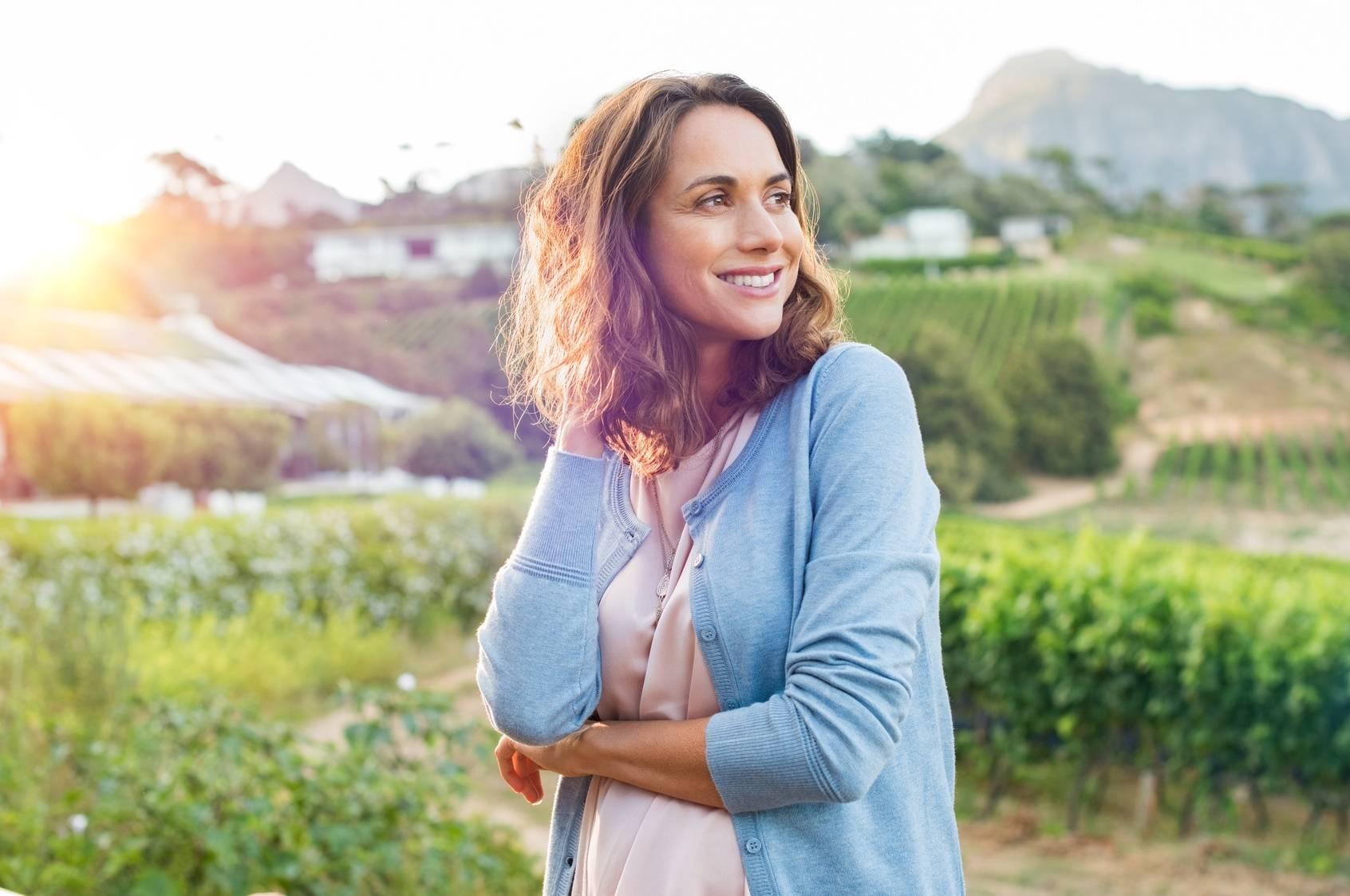 Niepłodność a miesiączka. Uśmiechnięta kobieta w niebieskim sweterku stoi na tle winnicy na prowincji.