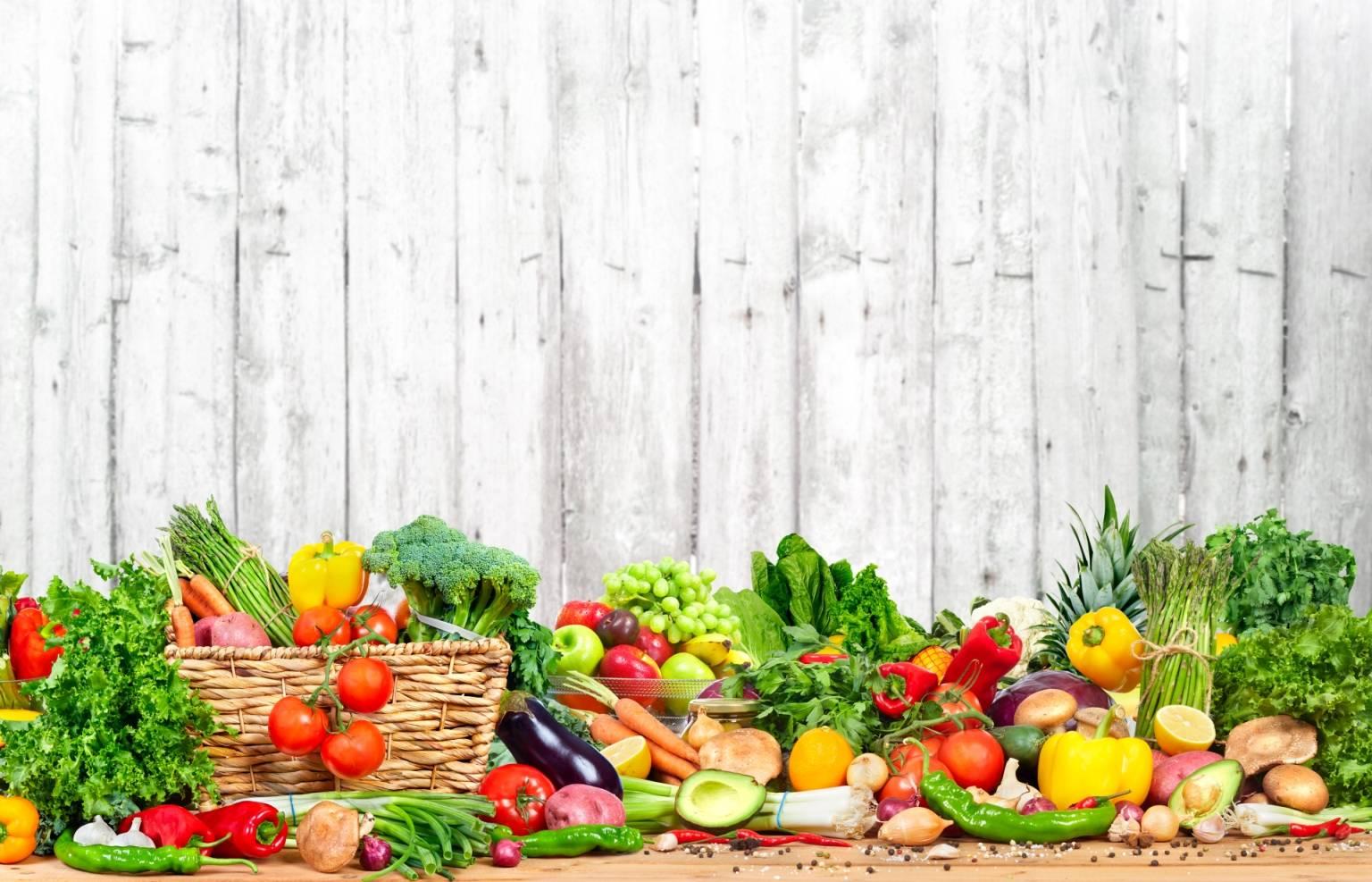 Jak poradzić sobie z cukrzycą typu 2? Pod płotem z szarej rustykalnej deski leżą warzywa i owoce.