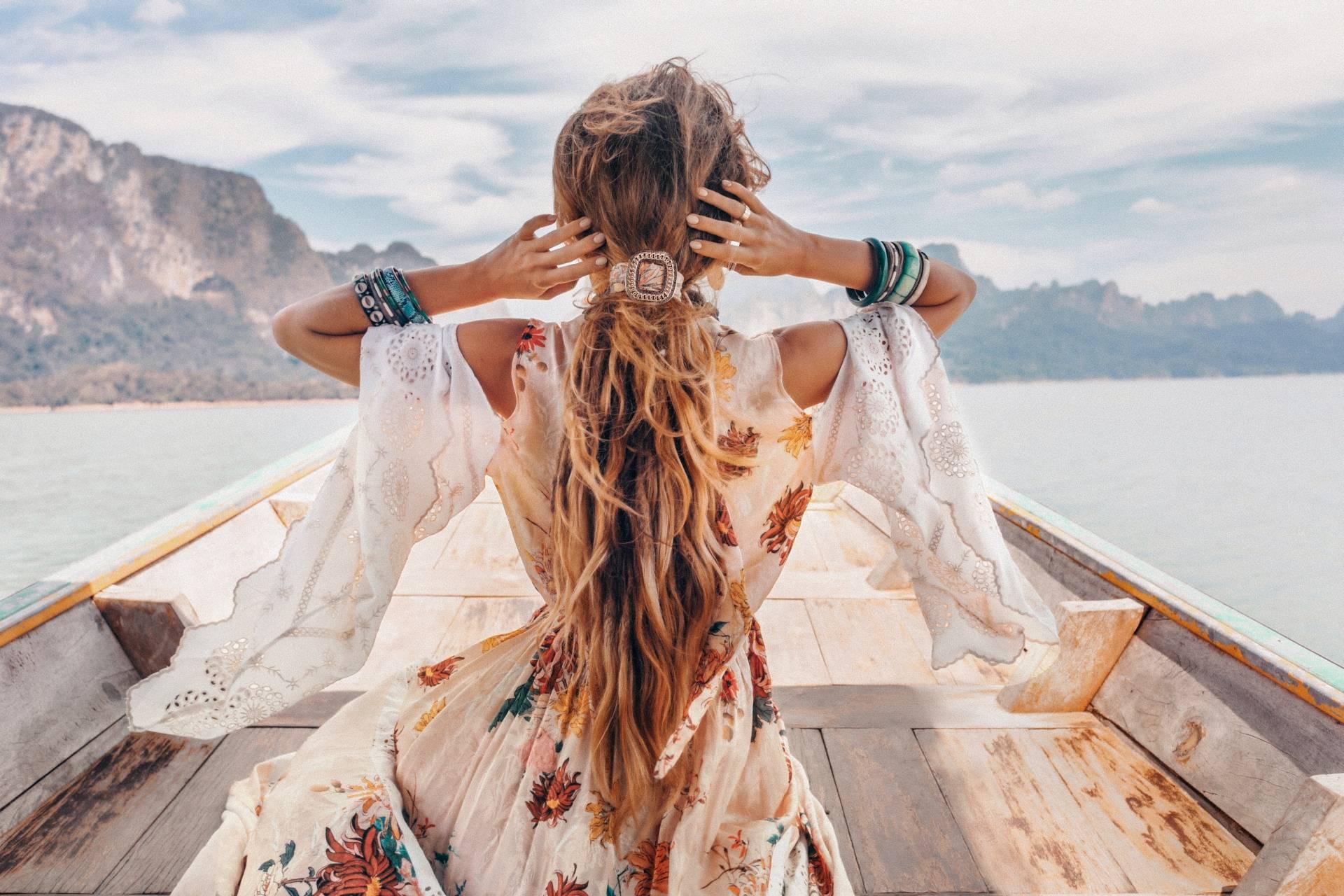 Kintsugi - jak zasklepić blizny na duszy i jak przygotować się na życiowe nieszczęścia. Dziewczyna w boho sukience płynie łódką, trzyma dłońmi długie blond włosy.