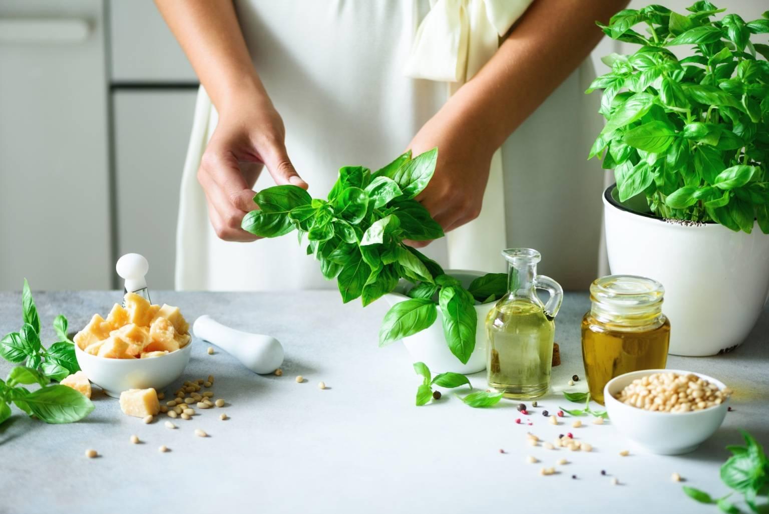 Kobieta przygotowuje posiłek w kuchni, trzyma w ręku bazylię. Na czym polega wegetarianizm?