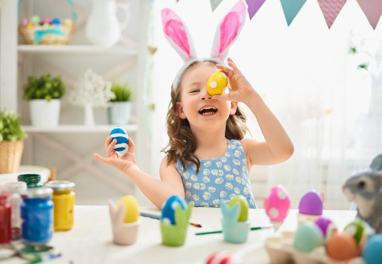 Przepisy na święta wielkanocne autorstwa Agnieszki Żelazko. Dziewczynka w opasce z uszami królika maluje pisanki w kuchni.