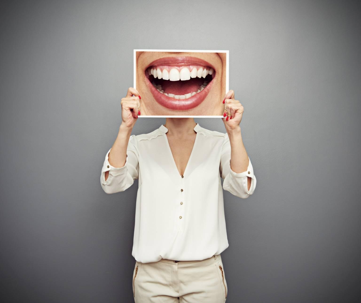 Naturalne sposoby na pleśniawki u dorosłych. Kobieta trzyma na wysokości twarzy zdjęcie uśmiechniętej buzi.