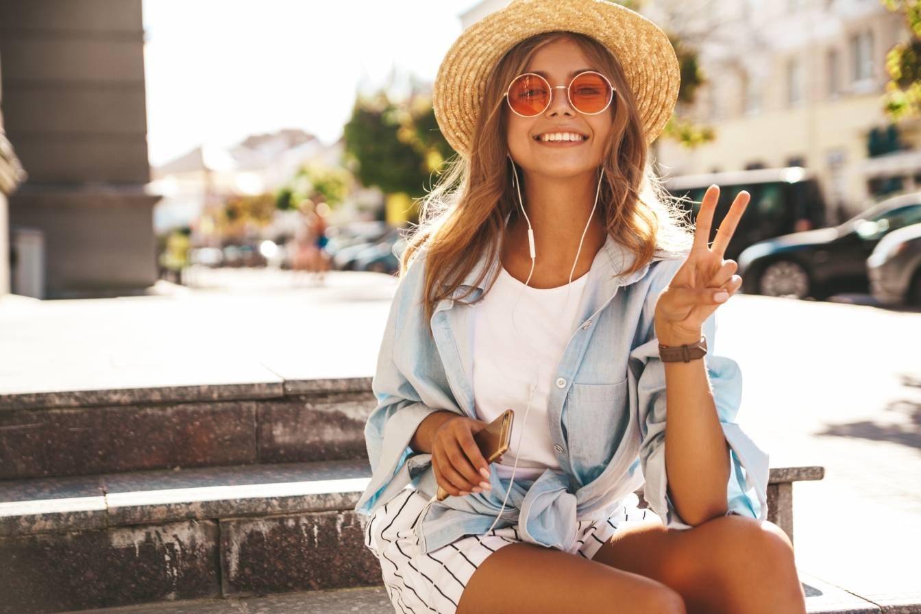 Jak dbać o włosy latem? Na czym polega pielęgnacja włosów zniszczonych słońcem? Młoda dziewczyna w letnim stroju, okularach przeciwsłonecznych i kapeluszu słomkowym siedzi na schodkach na placu miejskim i słucha muzyki na smartfonie.