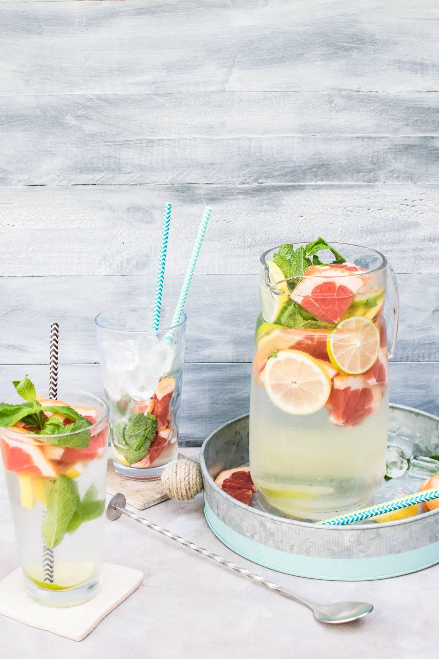 Owocowa lemoniada w dzbanku i szklankach z dodatkiem cytrusów i lodu. Ile wody pić latem? Co pić w upały?