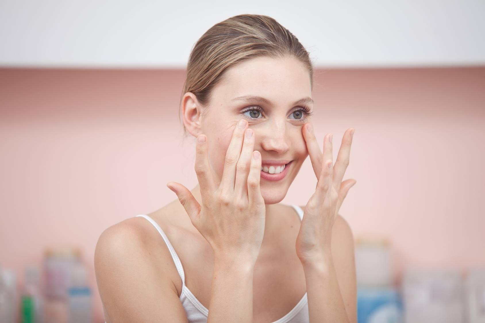 Obrzęk, opuchlizna, worki pod oczami - jak się ich pozbyć? Młoda kobieta w białym topie dotyka palcami worków pod oczami.