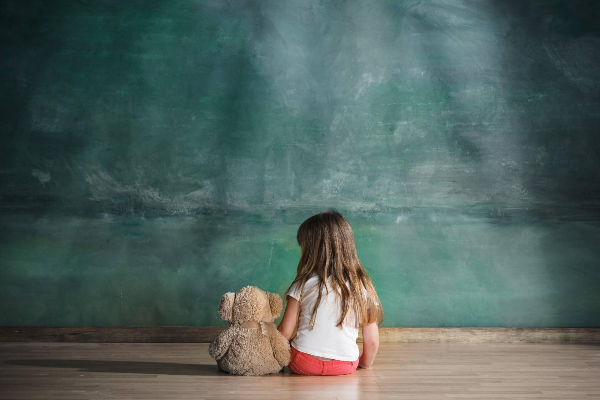 Wysoko wrażliwe dziecko. Mała dziewczynka siedzi na podłodze zwrócona przodem do ściany. Obok niej siedzi pluszowy miś.