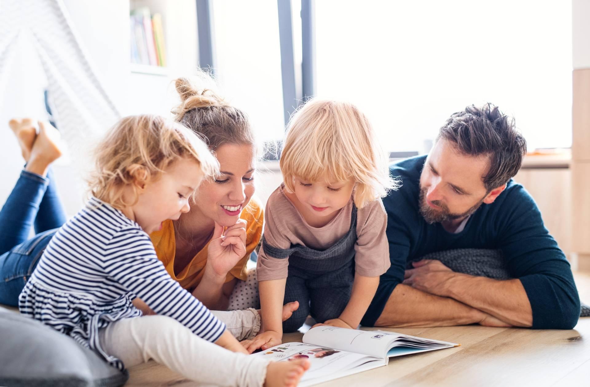 Rodzice czytają bajki wspólnie z dwójką swoich dzieci. Wspólne czytanie bajek dla dzieci.