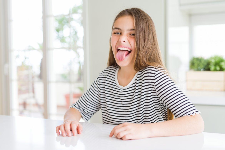 Zmiany na języku - o czym świadczy wygląd języka? Młoda dziewczyna w koszulce w paski siedzi przy blacie kuchennym i pokazuje język.