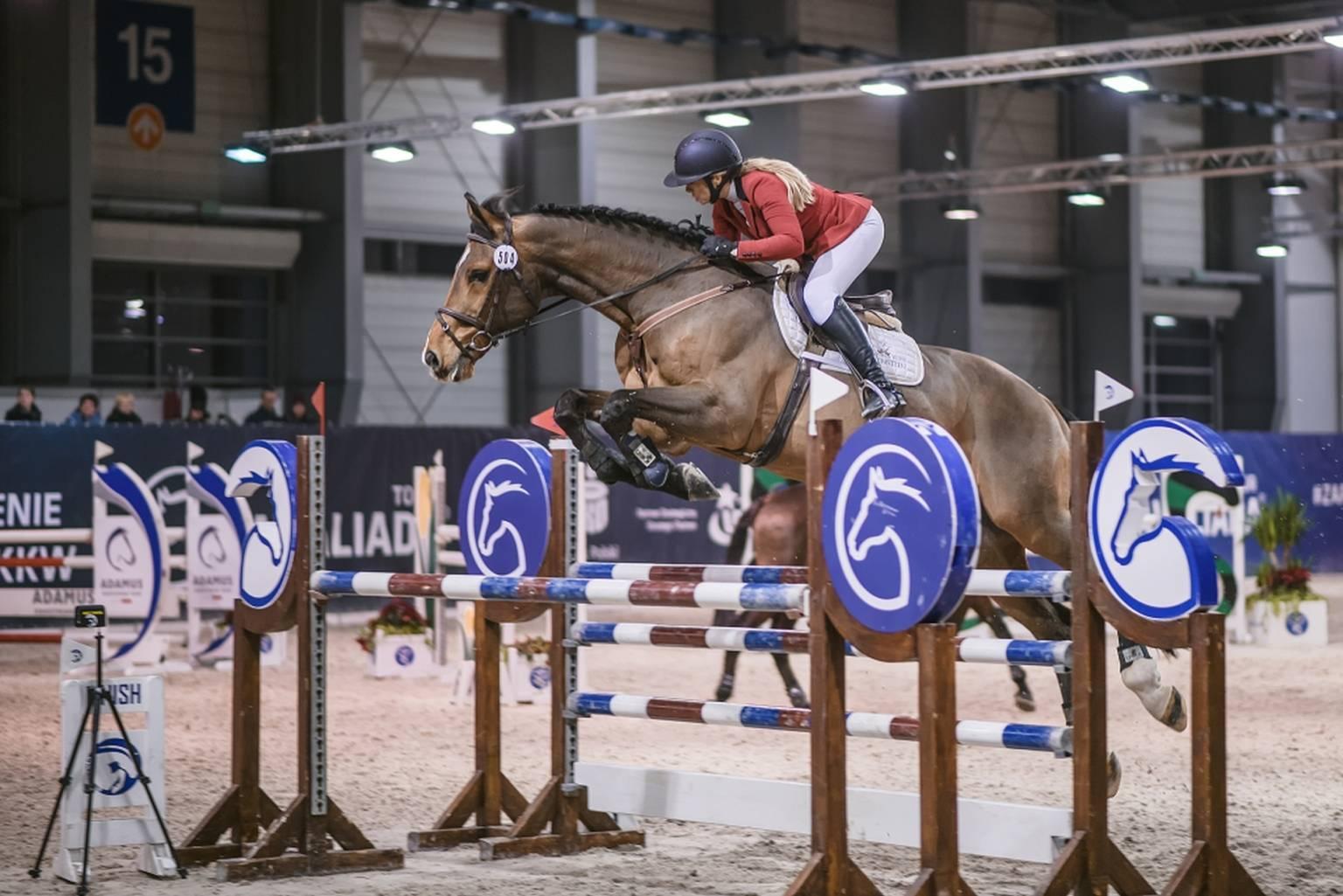 Karolina Ferenstein-Kraśko podczas zawodów jeździeckich przeskakuje z koniem przez przeszkody.