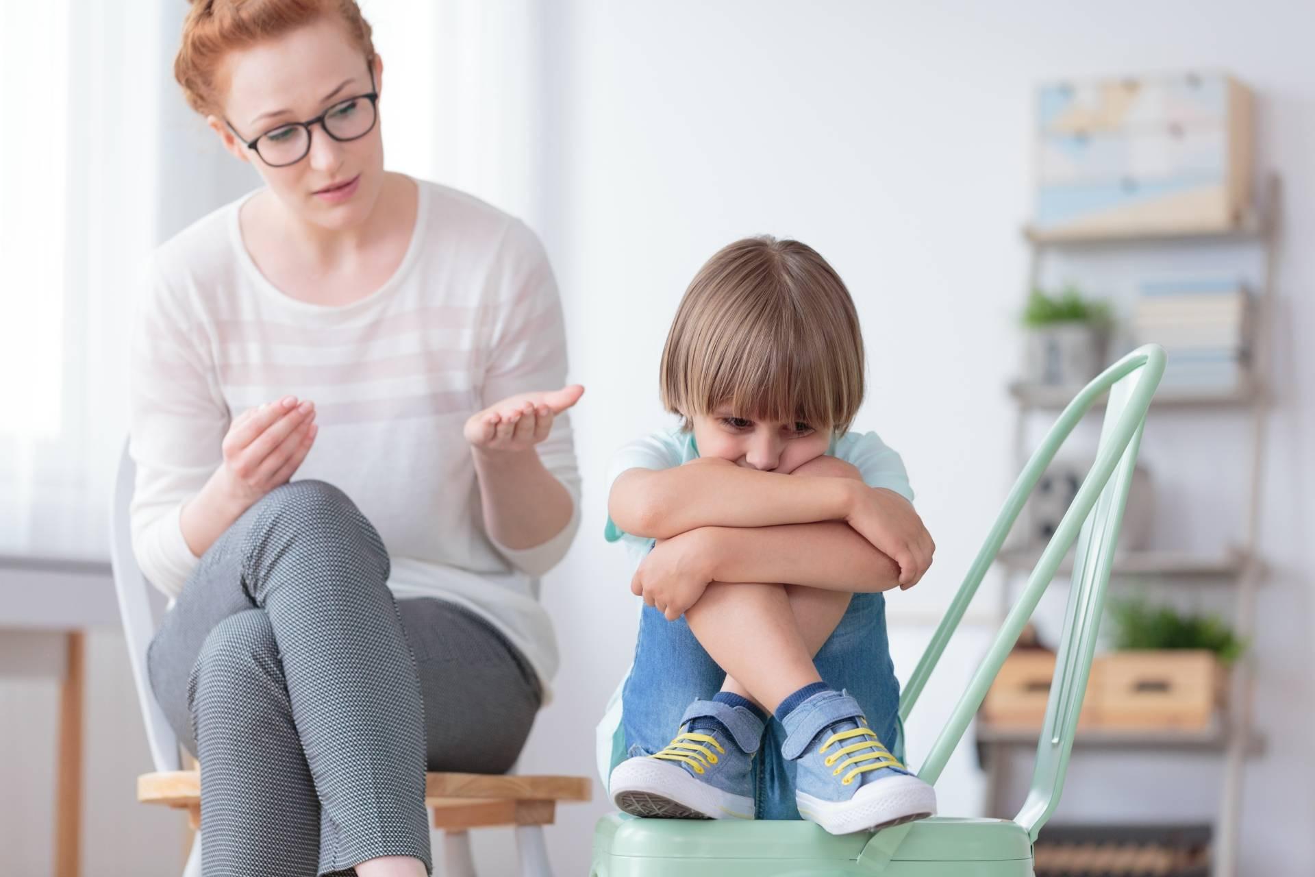 Wrażliwe dziecko. Obrażony chłopczyk siedzi z podkulonymi nogami na krześle, obok niego siedzi mama i tłumaczy mu coś.