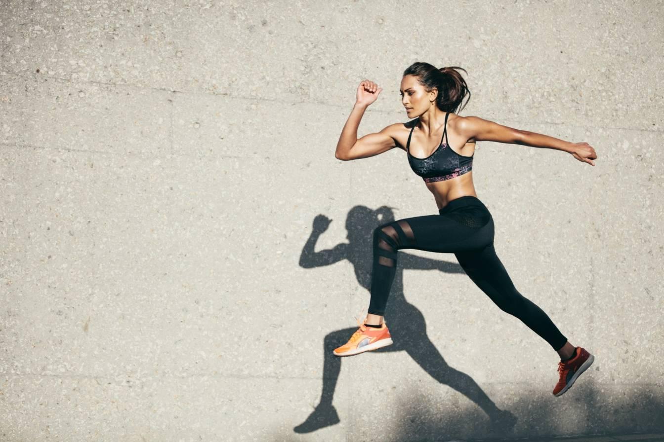 Sport amatorski/rekreacyjny a sport wyczynowy. Jakie są korzyści z uprawiania sportu, a jakie zagrożenia? Młoda wysportowana dziewczyna w stroju sportowym biegnie wzdłuż muru.