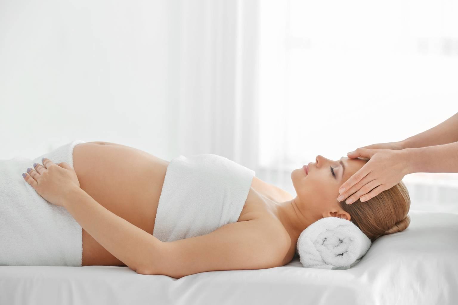 Medycyna chińska na dolegliwości w ciąży. Kobieta w ciąży podczas zabiegu akupunktury.