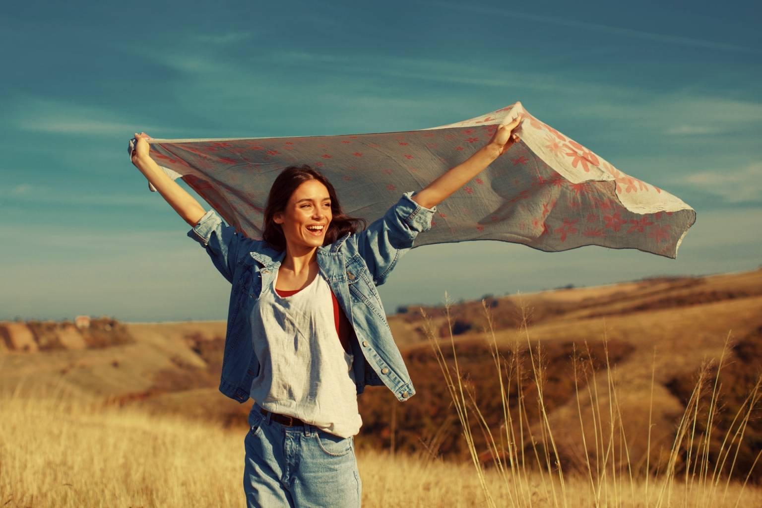 Odporność na stres - jak budować odporność psychiczną? Młoda kobieta stoi wśród łanów zbóż i unosi w górę powiewający na wietrze szal.