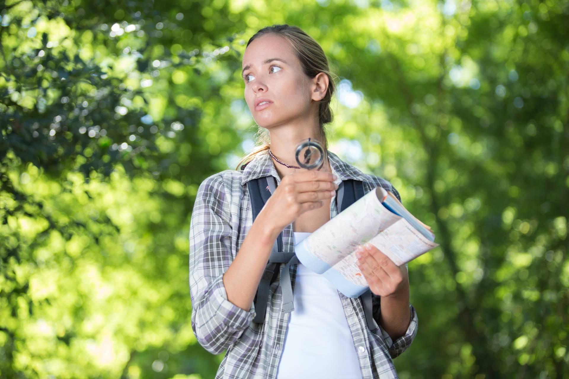 Zagubiona kobieta z mapą w ręku rozgląda się po lesie. Adam Wajrak tłumaczy jak nie zgubić się w lesie.