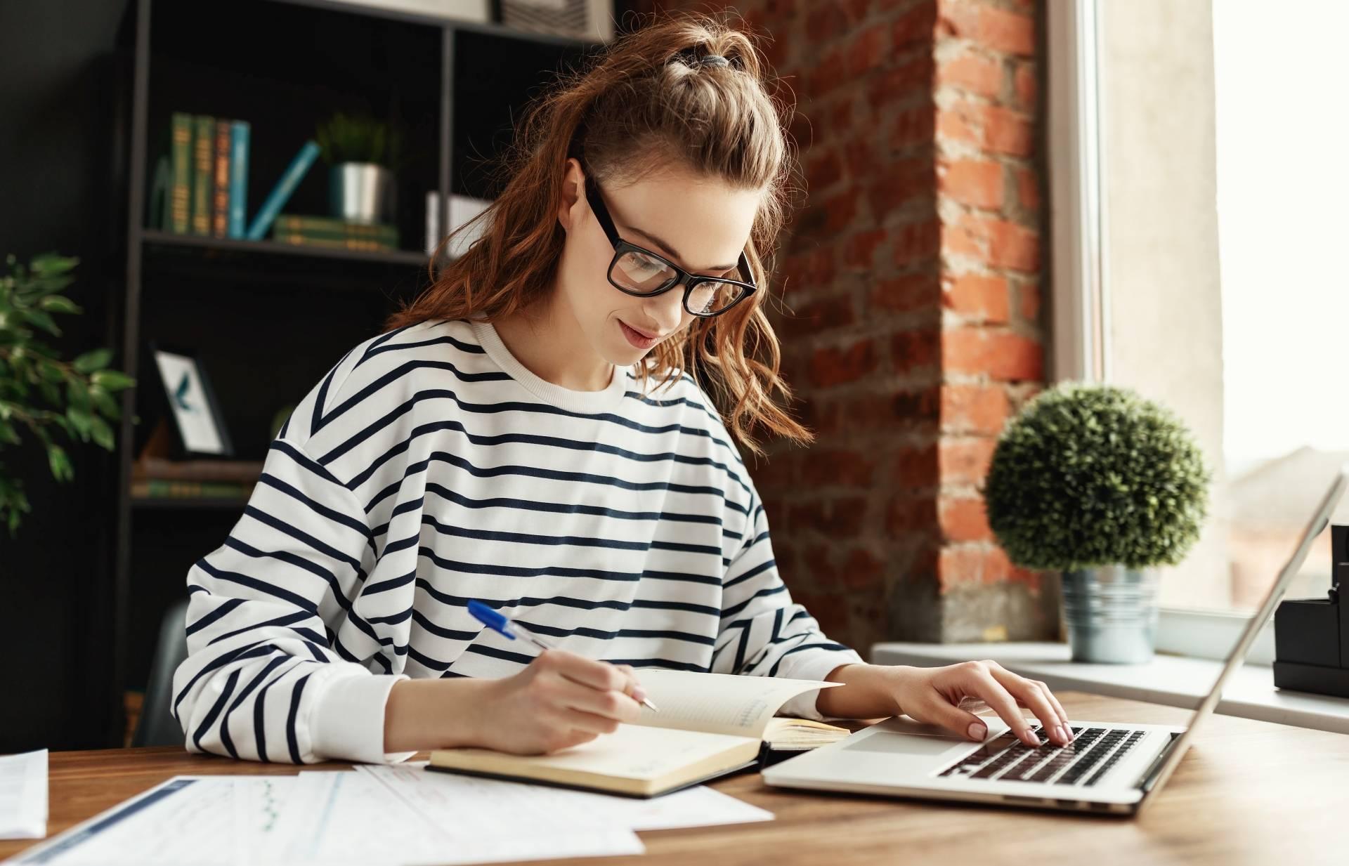 Work-life balance na home office. Młoda dziewczyna z pokolenia millenialsów w białej bluzce w czarne paski i okularach w rogowej oprawce siedzi przy laptopie i robi notatki w zeszycie.