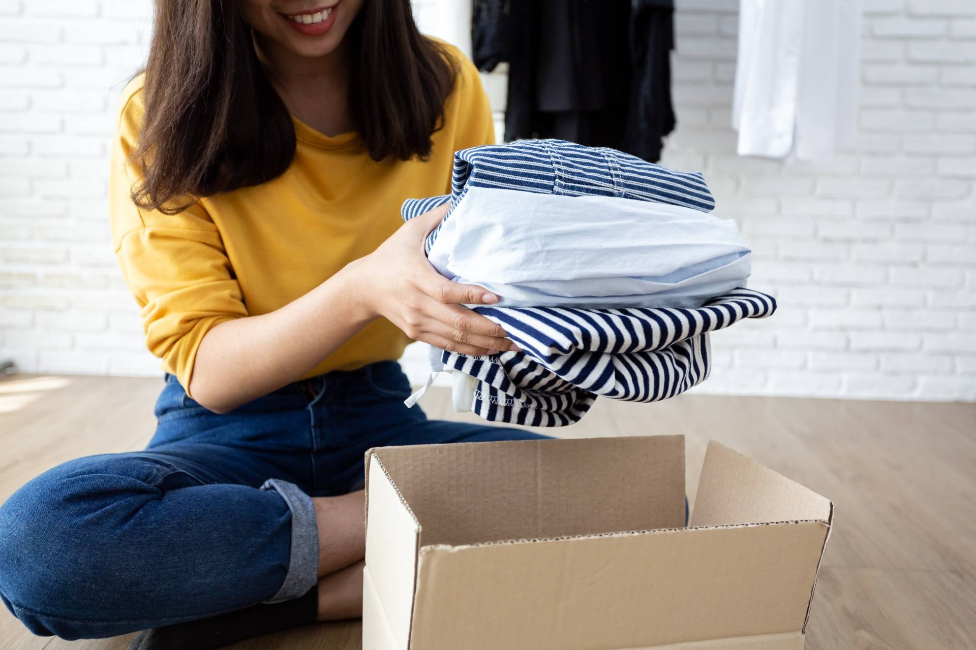 Porządki w szafie - gdzie oddać nienoszone ubrania? Kobieta w żółtej bluzce i jeansach wkłada ubrania do kartonu.