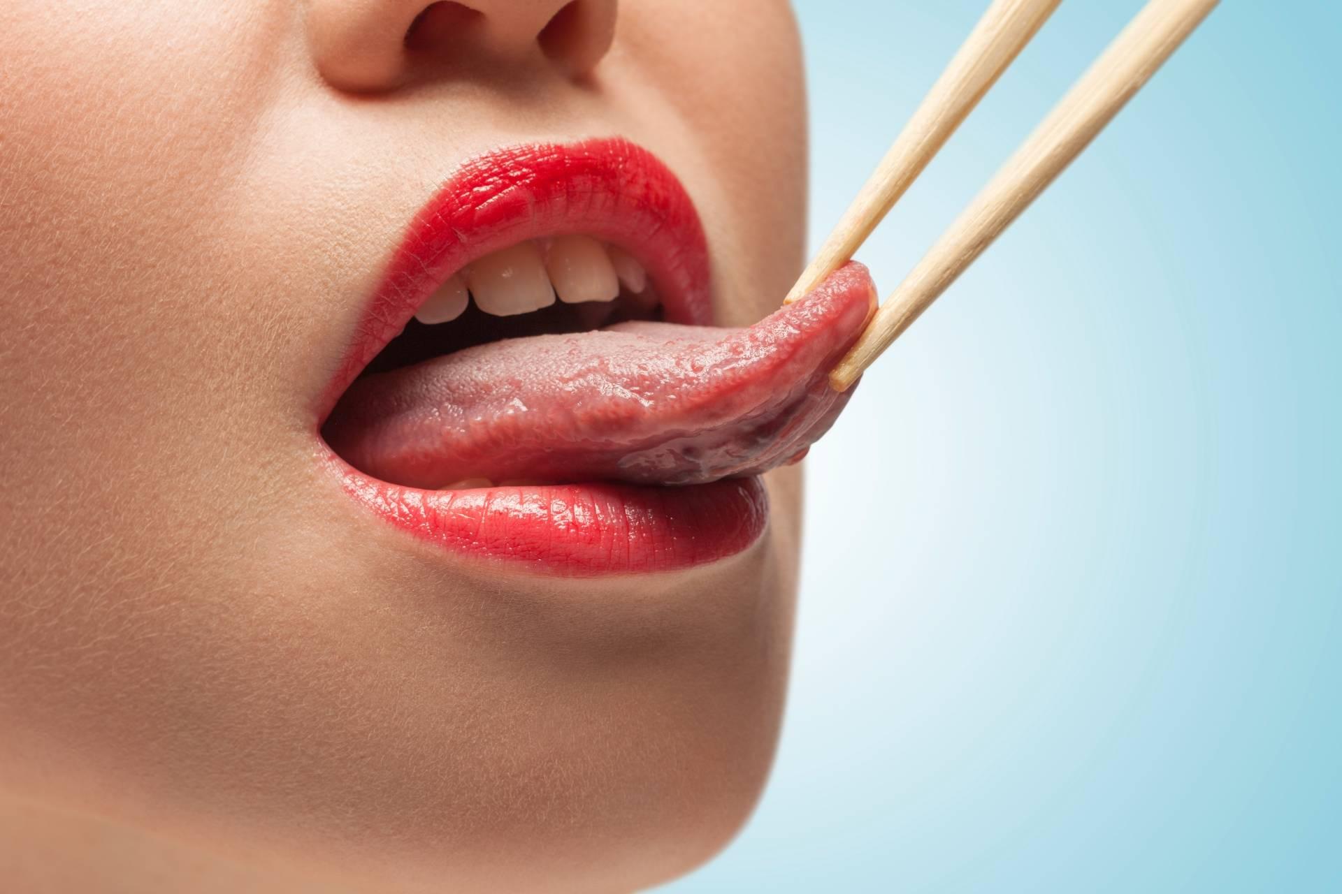 Jak wygląda zdrowy język? Zbliżenie na dolną część twarzy młodej kobiety, której język jest trzymany w patyczkach do sushi.