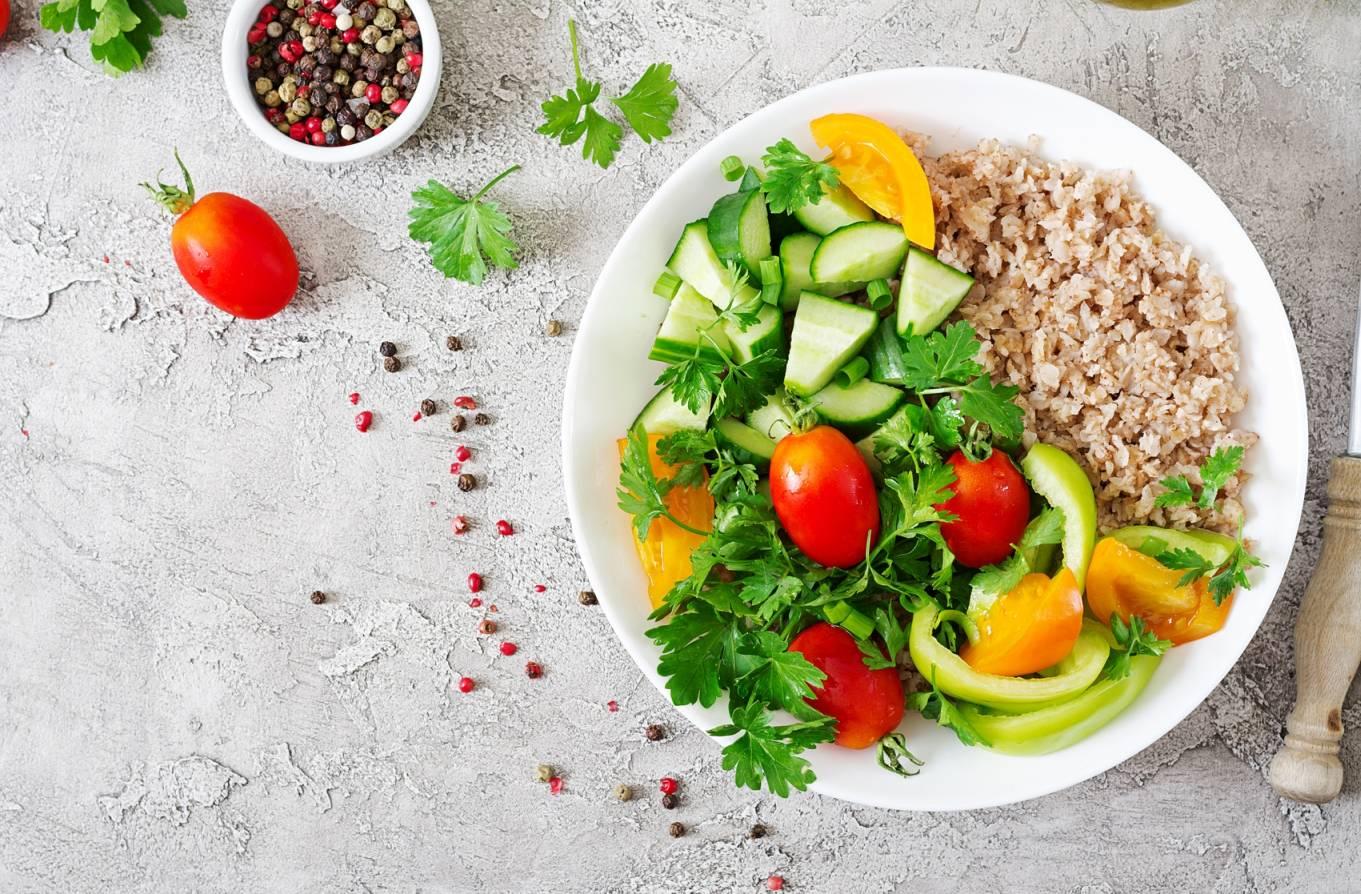 Zdrowa dieta pomaga zwalczać cukrzycę typu 2. Na białym talerzu leżą kolorowe surowe warzywa z kaszą. Talerz leży na betonowym blacie, obok miseczka z kolorowym pieprzem.