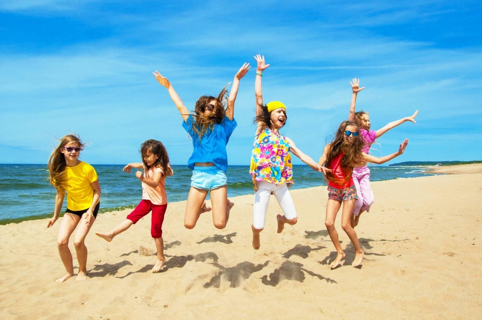 Zatrucie pokarmowe u dzieci - jak je leczyć? Szczęśliwe dzieci w kolorowych ubraniach pozują do zdjęcia na plaży podczas wakacji, skacząc do góry.