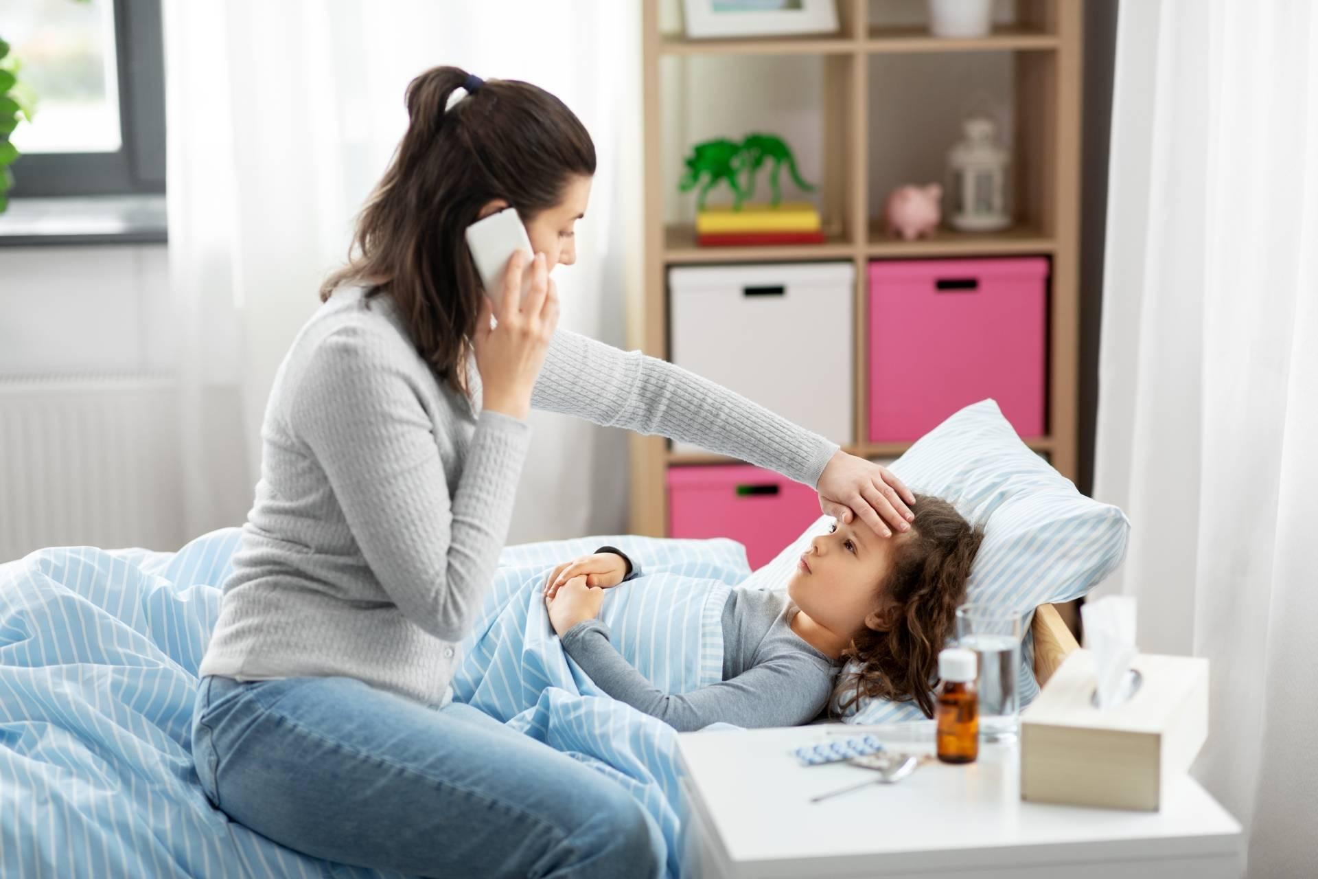 PIMS - zespół postcovidowy - jakie objawy powinny cię zaniepokoić? Mama mierzy temperaturę córce leżącej w łóżku i rozmawia przez telefon z lekarzem.