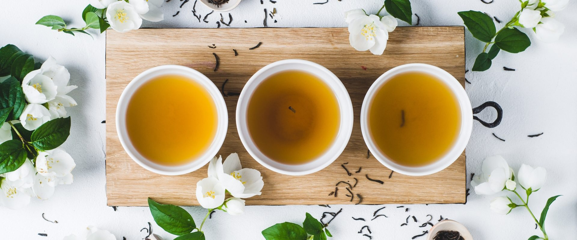 Zielona herbata - jakie domowe kosmetyki DIY można zrobić z zielonej herbaty? Zielona herbata w 3 filiżankach na drewnianej desce, wokół leżą listki herbaty i jaśmin.