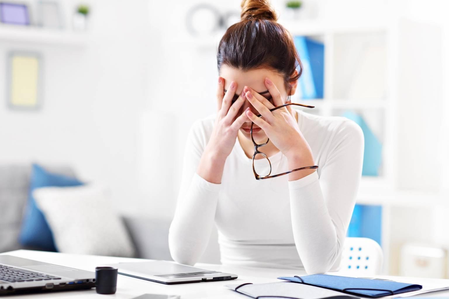 Siedzący tryb życia. Młoda zmęczona kobieta w białej bluzce siedzi przy biurku i trzyma głowę w dłoniach.
