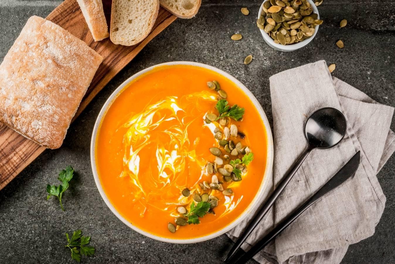 Dieta na przeziębienie wg medycyny chińskiej - co jeść , gdy dopadnie nas atak zimnego wiatru? Ujęcie z góry na miskę zupy dyniowej ze śmietaną, leżącą na szarym blacie, obok leżą deska z chlebem, ścierka i szczućce.