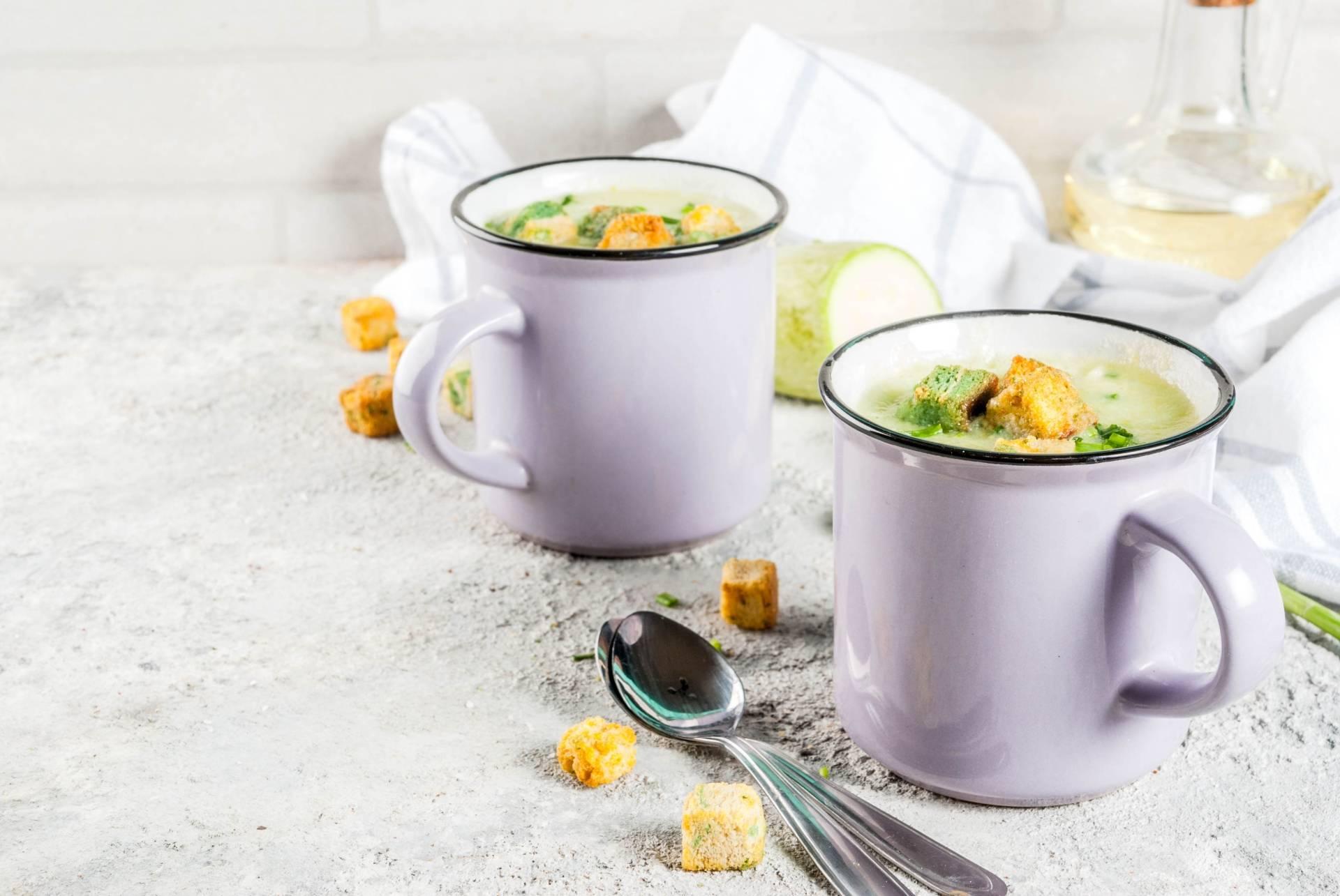 Zupa z cukinii w dwóch białych emaliowanych garnuszkach stojących na białym blacie, obok leżą 2 łyżki i rozrzucone grzanki.