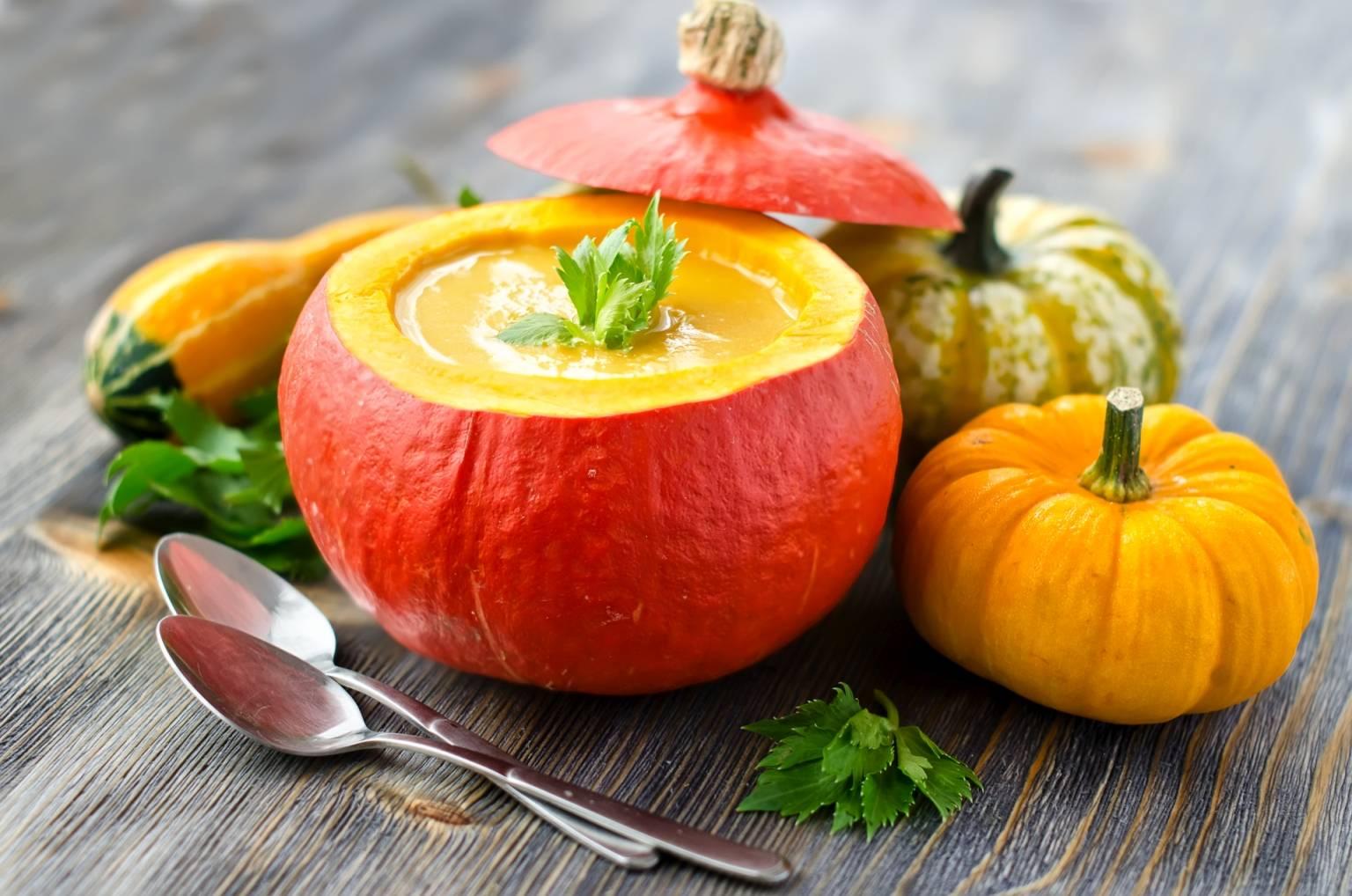 Zupa dyniowa - przepis na dobry krem z dyni. Zupa podana w wydrążonej okrągłej dyni, obok leżą łyżki i inne odmiany dyni.