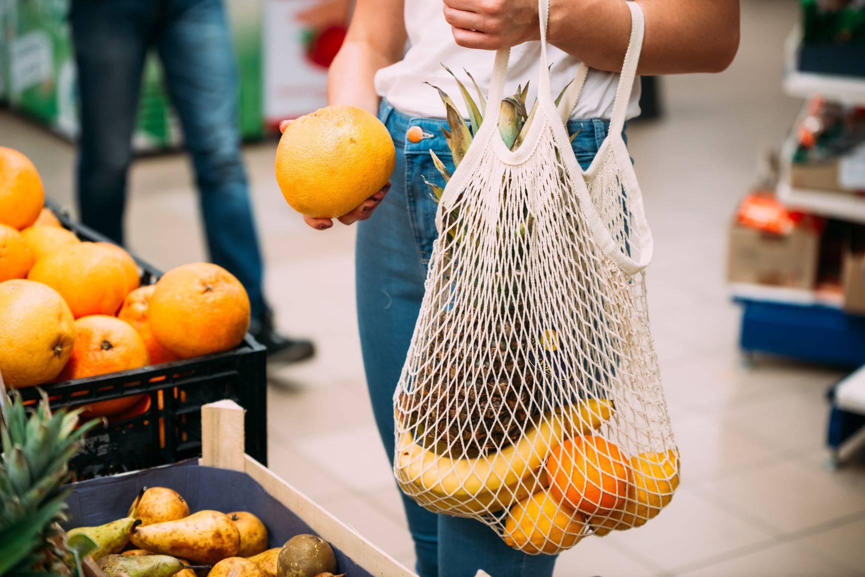 Jak być eko? Jak zacząć żyć ekologicznie w duchu zero waste? Kobieta robi zakupy na targu i wkłada owoce do ażurowej torby ekologicznej.