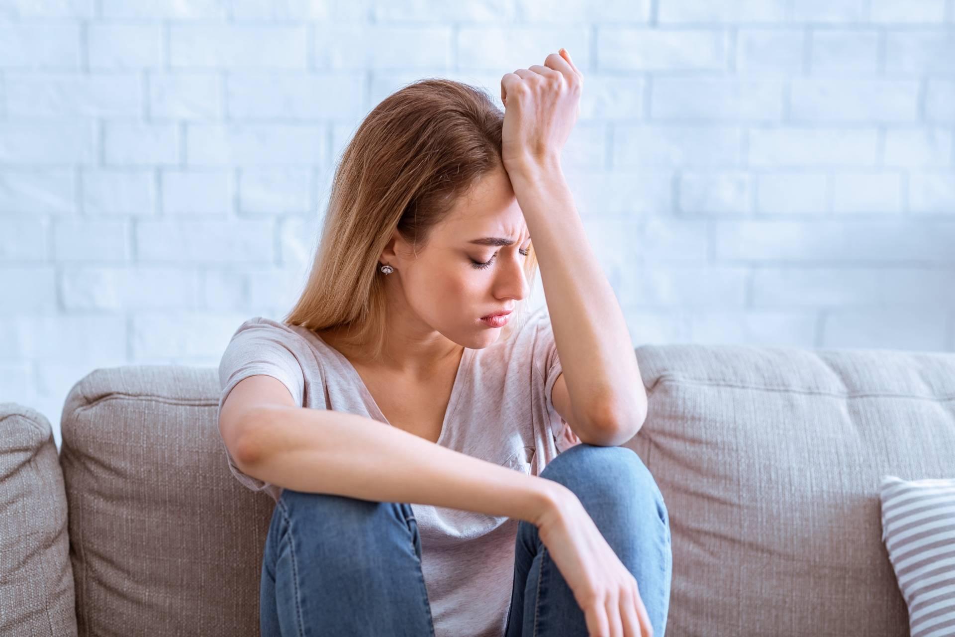 Work-life balance - co zrobić, gdy przychodzi życiowy kryzys i depresja? Smutna młoda kobieta siedzi na kanapie, opiera łokcie na podciągniętych kolanach i trzyma się za głowę.